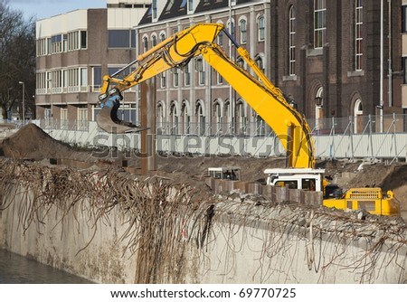 Excavator at an urban demolition site - stock photo