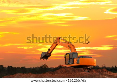 Excavator at construction site with golden sky sunset  in the evening - stock photo