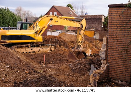 Excavator at demolition site in abandoned town in Germany. In this place will be a coal open-pit mine soon. - stock photo