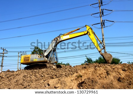 Excavator at meadow with heap of ground - stock photo