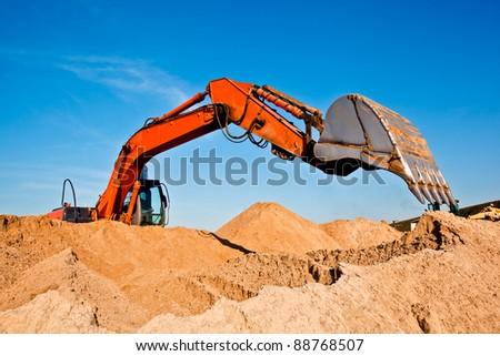 Excavator at sand quarry - stock photo