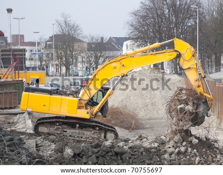 Excavator at urban demolition site - stock photo