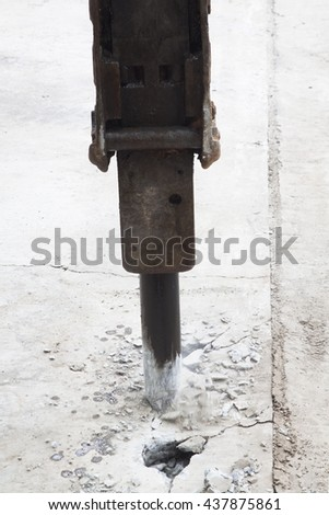 Excavator breaking and drilling the concrete road for repairing. - stock photo