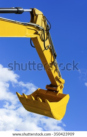 Excavator bucket, bulldozer shovel, hydraulic piston system of yellow construction vehicle isolated on blue sky with white clouds  - stock photo
