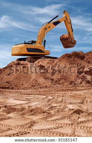 Excavator bulldozer in sandpit with raised bucket filled of sand over blue cloudscape sky - stock photo