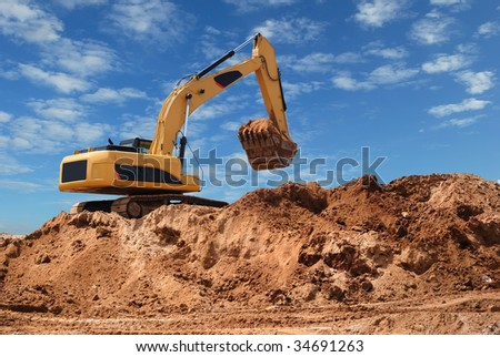 Excavator bulldozer in sandpit with raised bucket over blue cloudscape sky - stock photo