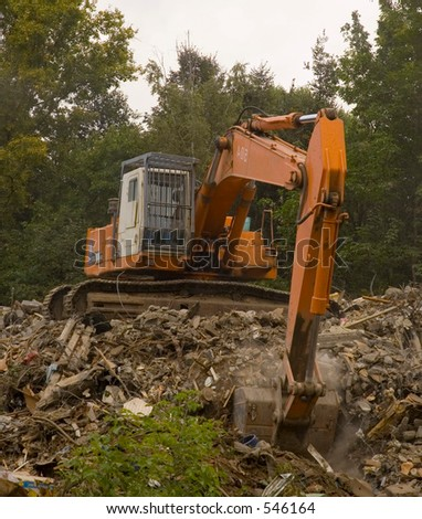 Excavator cleaning rubble - stock photo