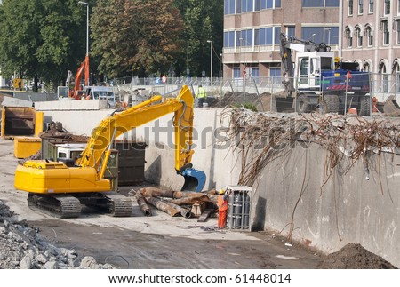 Excavator demolishing a reinforced concrete wall of a highway flyover while a worker wearing protective clothing and safety helmet is monitoring gas cylinders - stock photo