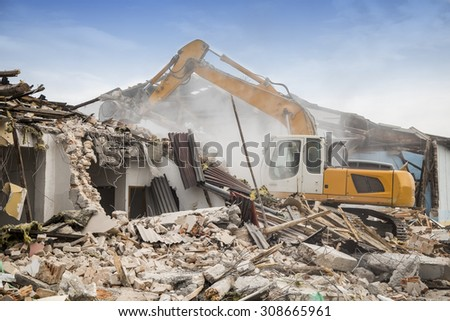 Excavator demolishing barracks for new construction project. Made with shallow depth of field. - stock photo