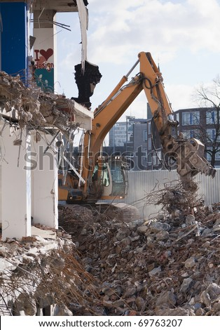 Excavator demolishing derelict building - stock photo
