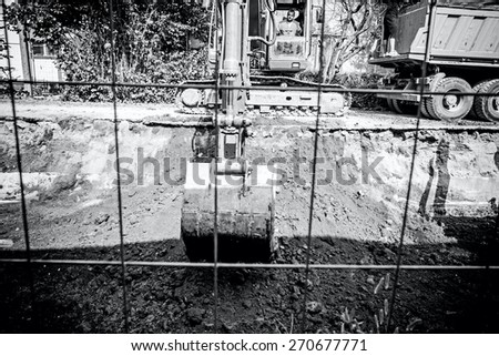 Excavator digging a deep trench in city street. - stock photo