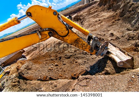 Excavator digging a hole and loading a dumper truck with soil in construction site - stock photo