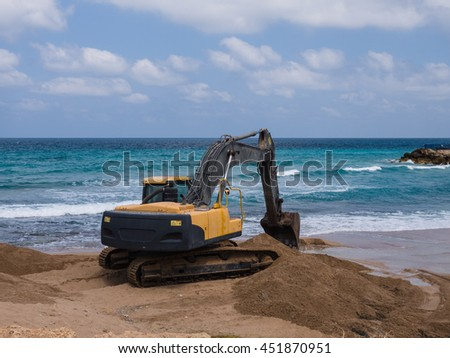 Excavator digging along the beach - stock photo