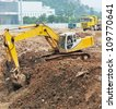excavator digging at construction site - stock photo