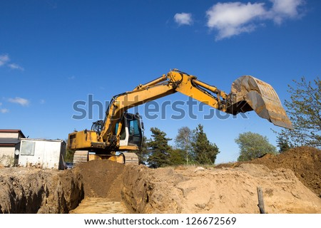 excavator digging sewer trench in construction site - stock photo