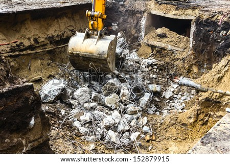 Excavator digging up the remains of a broken reinforced concrete - stock photo