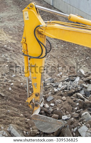 Excavator digs dirt, asphalt and gravel. - stock photo