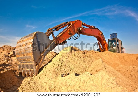 Excavator during earth moving works outdoors at sand quarry - stock photo