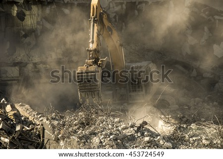 Excavator, earthmover surrounded with concrete debris and clouds of dust  - stock photo