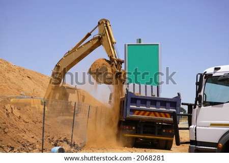 Excavator fillling a dump truck with sand - stock photo