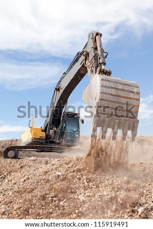 excavator flattening a road - stock photo