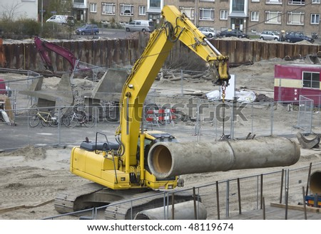 Excavator hoisting a sewer pipe - stock photo