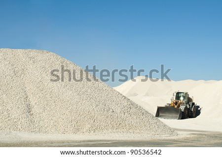 Excavator in a limestone quarry.Piles of limestone rocks - stock photo