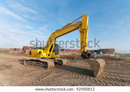 excavator in front of a newly build residential area - stock photo