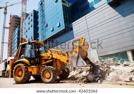 excavator is digging rubble in front of a modern building in construction - stock photo