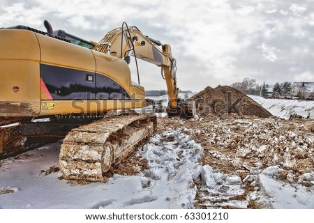 excavator loader at a construction building area  during winter. This is a HDR Image. - stock photo