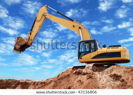 Excavator loader at construction site with raised bucket over blue sky - stock photo