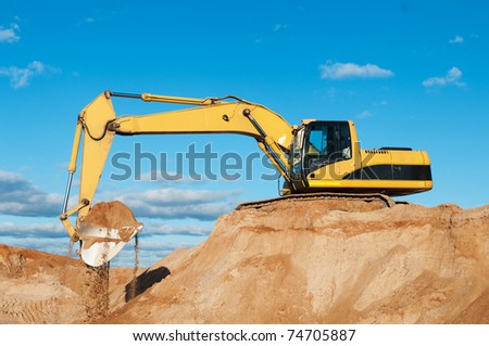 excavator loader during earthmoving works outdoors at construction site - stock photo