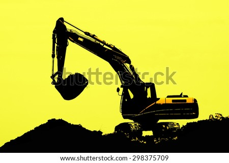 Excavator loader machine during earth moving works outdoors at construction site, silhouette