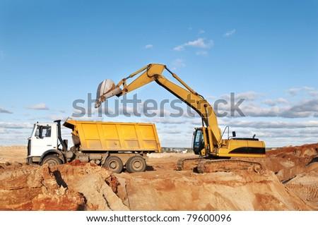 excavator loader machine loading dumper truck at sand quarry - stock photo