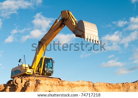 excavator loader machine with risen boom construction site - stock photo