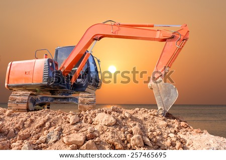 Excavator loader machine with sunset background - stock photo