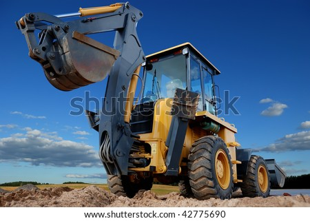 Excavator Loader with raised backhoe standing over cloudscape sky - stock photo