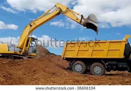 Excavator loading dumper truck tipper in sand pit over blue sky - stock photo
