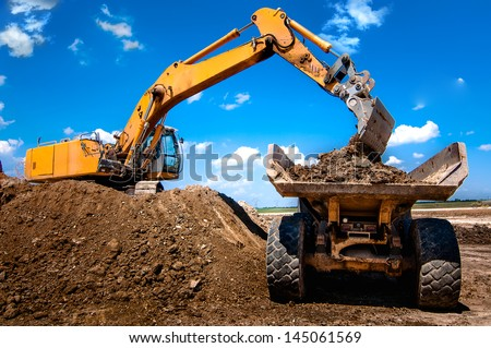 Excavator loading dumper truck tipper in sandpit in highway construction site - stock photo
