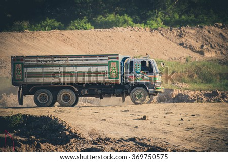 Excavator loading dumper truck tipper in sandpit in highway construction site , Yellow excavator loading soil into a dumper truck on construction site  - stock photo