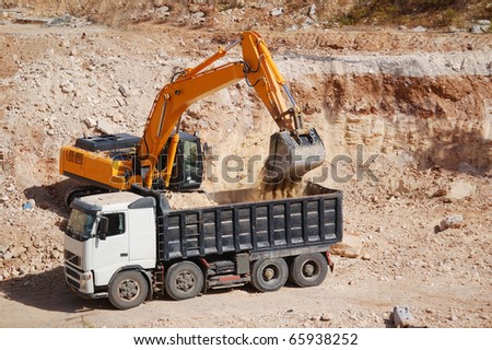 excavator loading dumper truck with sand at construction site - stock photo