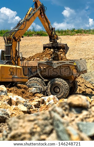 Excavator loading heavy duty dumper truck with rocks on construction site - stock photo