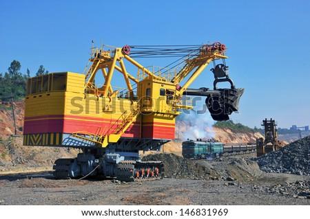 Excavator loading iron ore into goods wagon on the iron ore opencast mine - stock photo