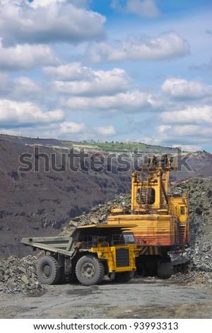 Excavator loading iron ore into the heavy dump truck on the iron ore opencast mining - stock photo