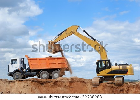 Excavator loading sand in rear-end tipper - stock photo