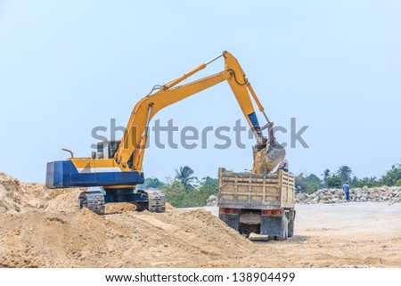 excavator loading sand on dumper truck at dolomite mines site - stock photo