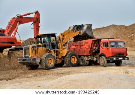Excavator loading tipper truck on a construction site - stock photo