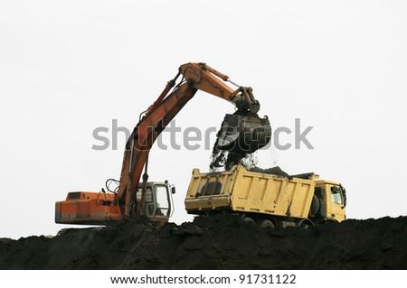 Excavator loading truck. White isolated - stock photo