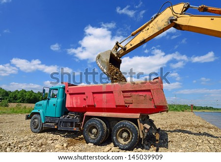 Excavator loads gravel car - stock photo