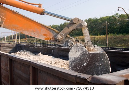 excavator loads gravel into the car of a train